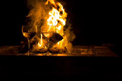Two wineglasses by the campfire in this picturesque romantic scene